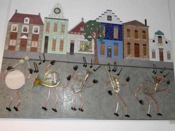 Toepasselijke kunst aan de muur van verenigingsgebouw In Harmonie. In het kunstwerk zijn niet alleen muziekinstrumenten, maar ook foto's en herinneringen van leden van Harmonie Wierden verwerkt.
